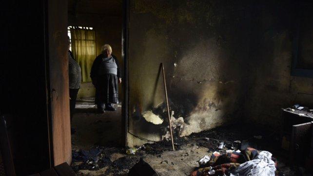 Una hermana de las víctimas muestra los daños materiales que dejó el incendio.