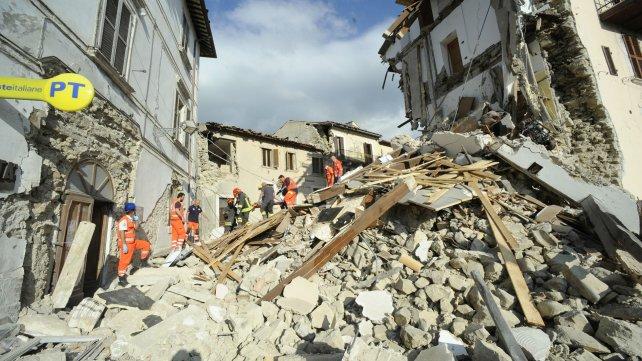 Los rescatistas llevan en camilla a una de las víctimas a través de un edificio en ruinas en Arquata del Tronto.