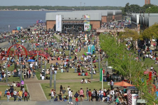 Una multitud disfruta de una jornada soleada al aire libre junto al río.