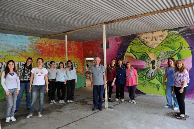 Los integrantes del proyecto, delante del mural pintado en el ingreso al comedor.