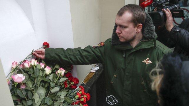 Alexander, ex miembro del Conjunto Alexandrov, pone flores en el edificio del coro militar en Moscú.