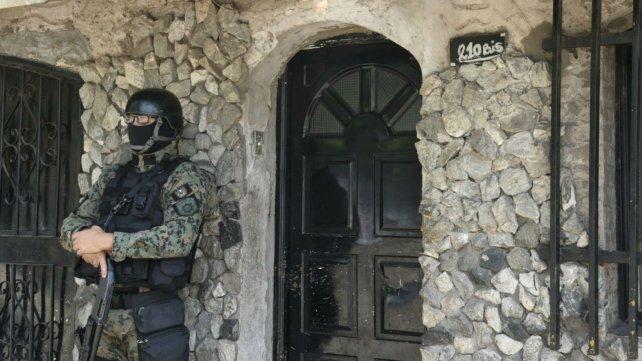 Policías de Infantería custodia uno de las casas allanadas esta mañana.