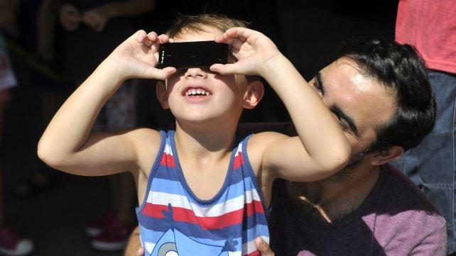 Chicos y grandes se acercar a ver el eclipse desde el Planetario.