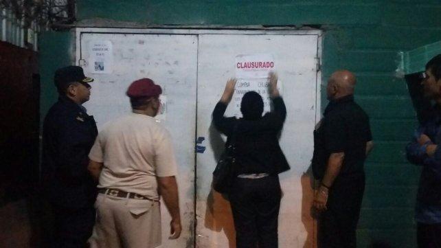 Los inspectores municipales colocan la faja de clausura.