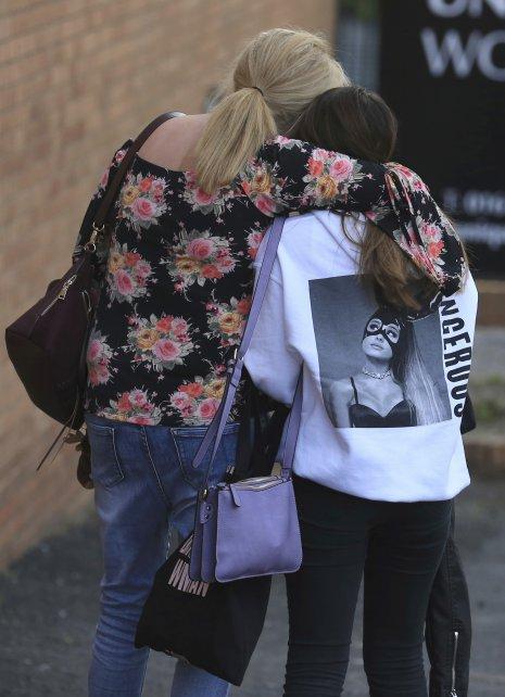 Una fan adolescente junto a su madre tras el atentado de anoche.