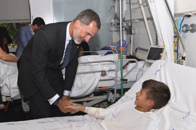 El rey Felipe saluda a uno de los niños que sufrieron heridas en el atentado.