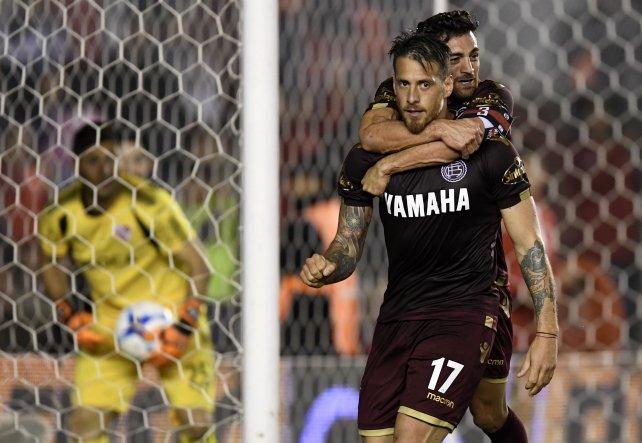 Denis ya convirtió el gol de penal y Lautaro Acosta se suma al festejo. El delantero no lo festejó por respeto.